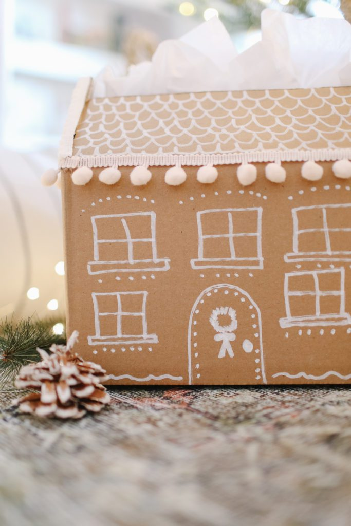 The cutest little gingerbread house gift box made from a regular corrugated cardboard shipping box.