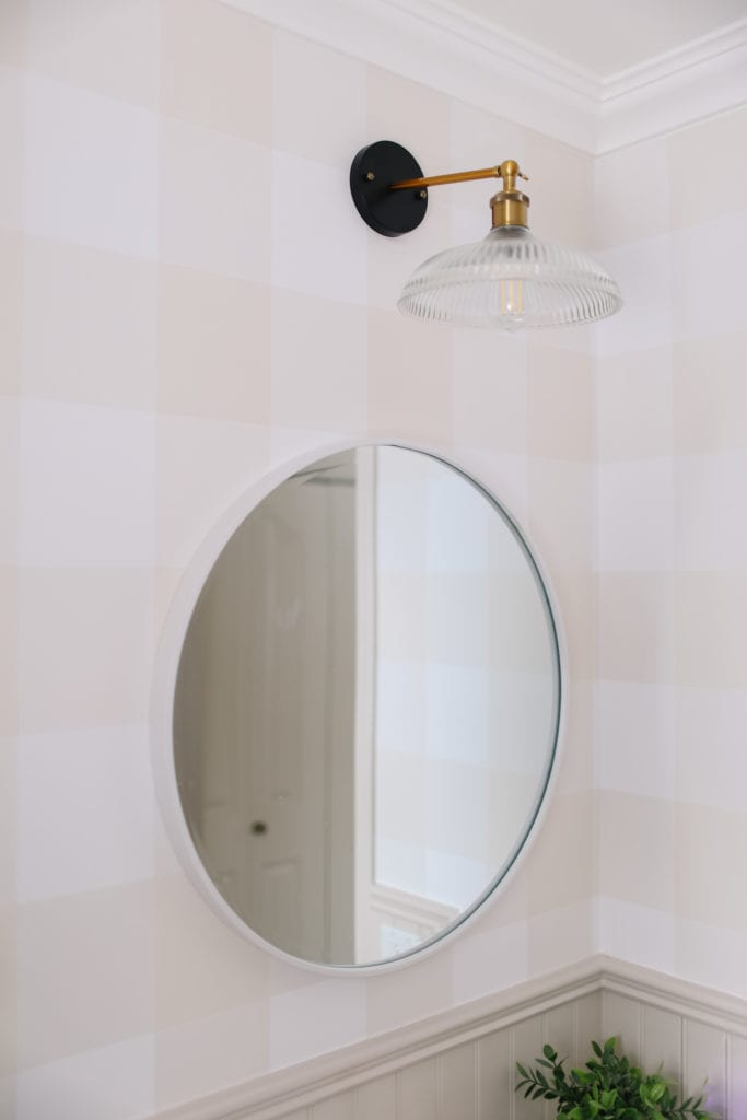 Round White mirror on plaid wallpaper in english country style bathroom