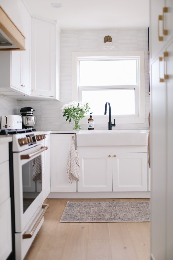 White tiny kitchen with gold hardware, white subway tile and black faucet