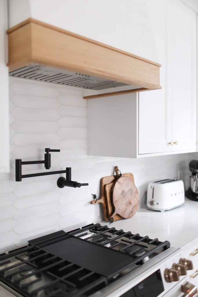 Custom range hood with vent insert in white kitchen with white backsplash tile and black pot filler faucet