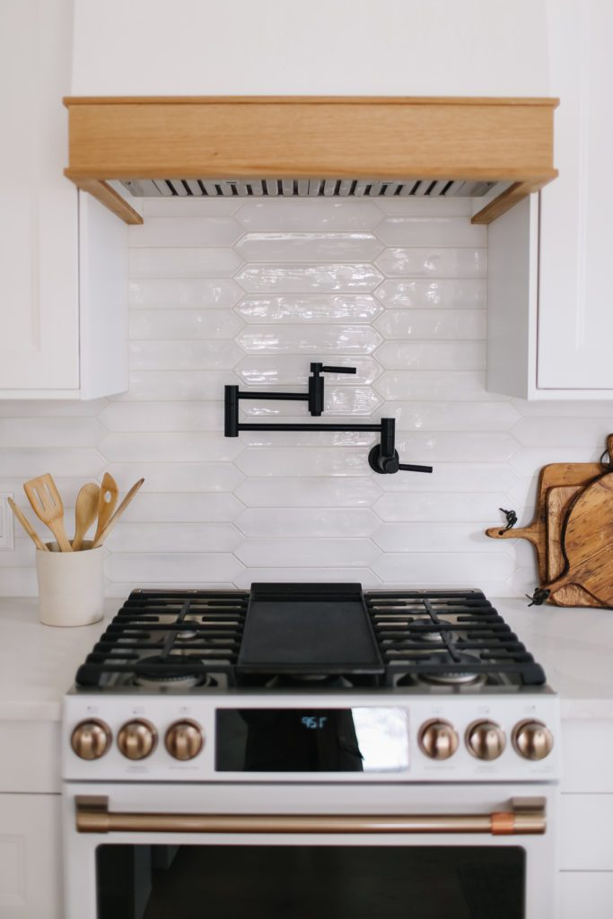 Custom range hood and black pot filler faucet in tiny white kitchen