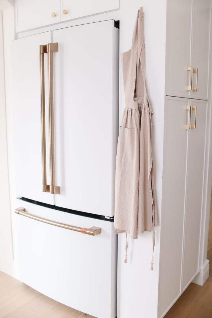 Counter depth cafe appliance french door fridge with gold handles in tiny white kitchen