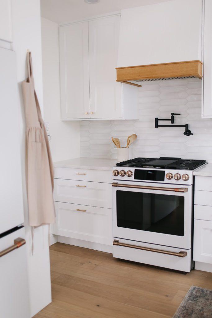 pretty white kitchen with gas range and custom range hood