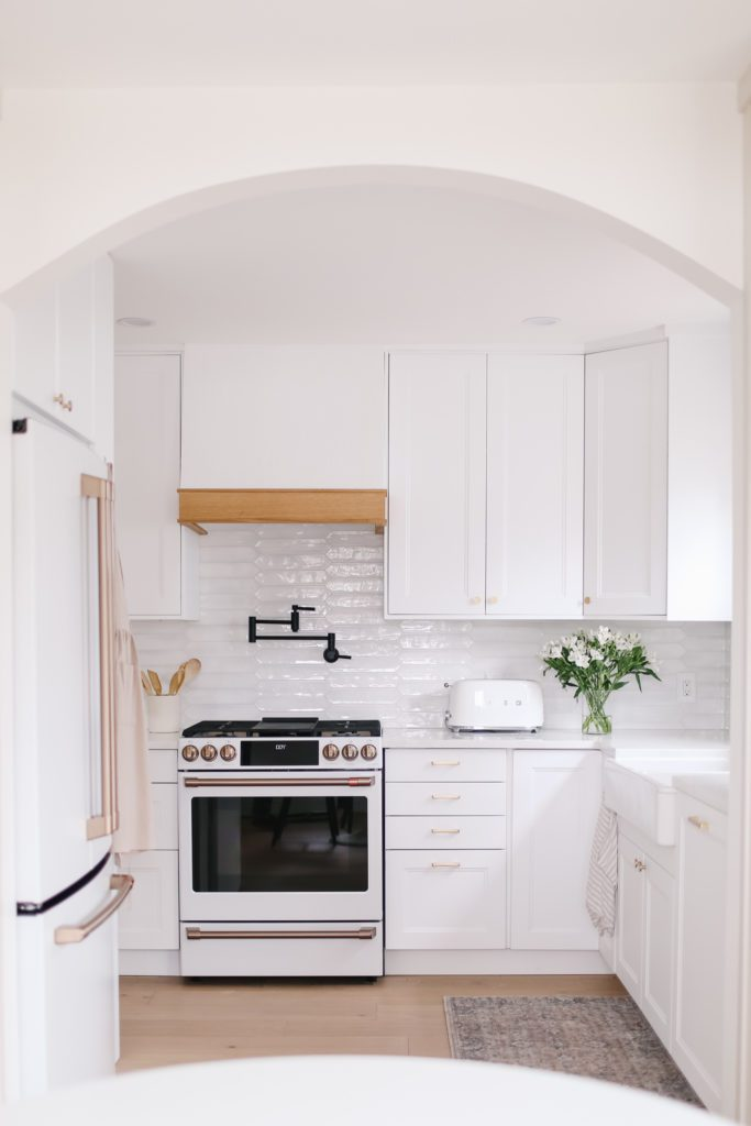 tiny kitchen with white cupboards, white backsplash tile and café appliance