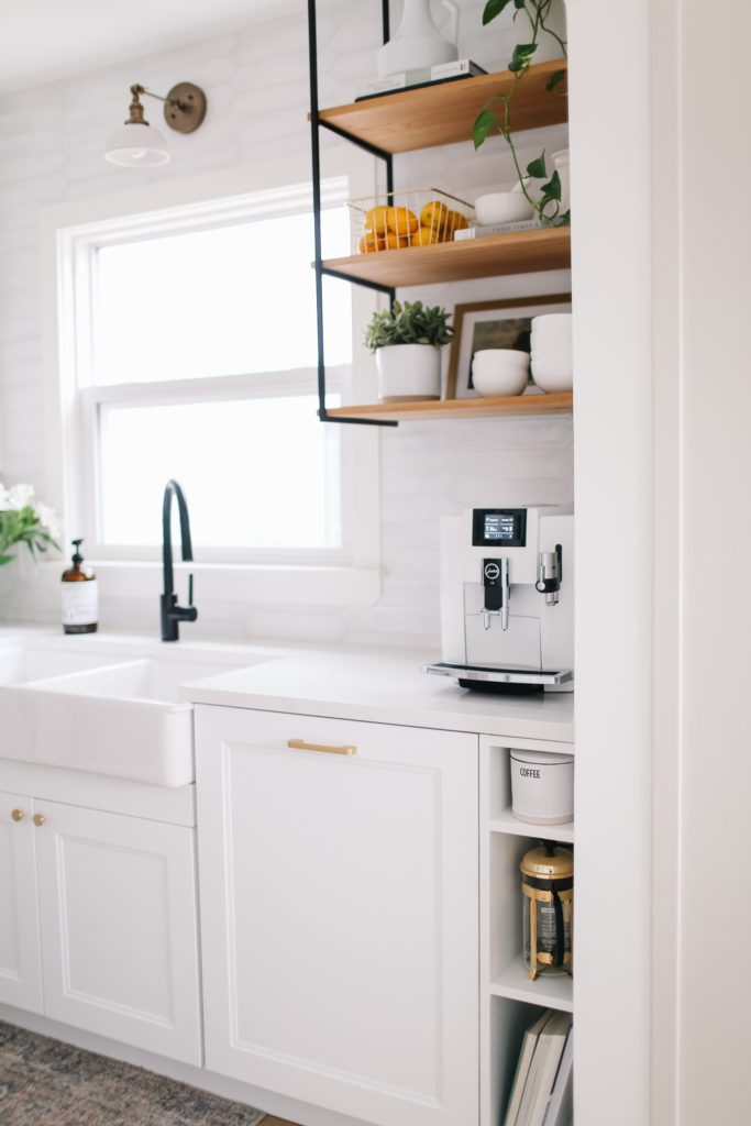 white kitchen cabinets and gold hardware with coffee maker on counter