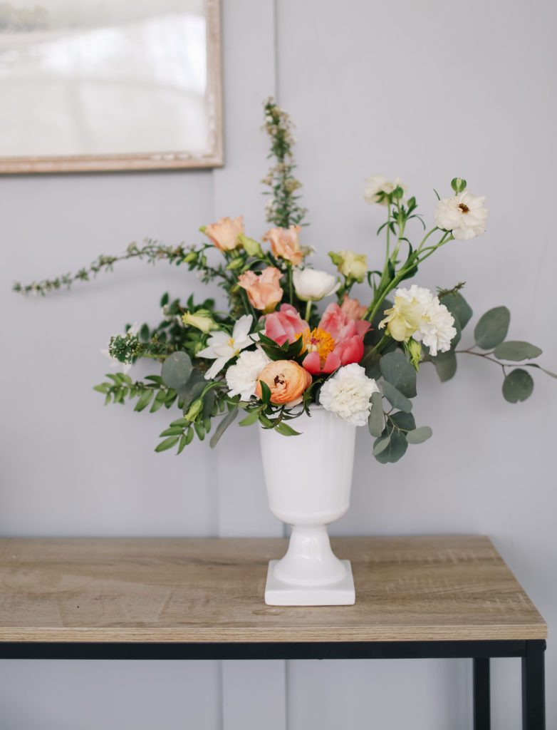Perfectly undone floral arrangement with loosely arranged pink and white florals and green stems