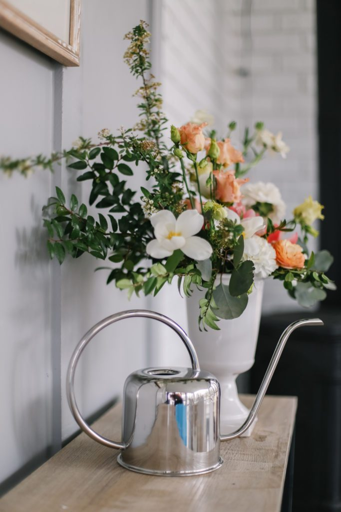 A natural looking floral arrangment with a silver watering can beside it on a table.