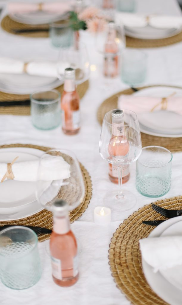 Simple Mother's Day tablescape with white dishes, wine glasses and pink water bottles