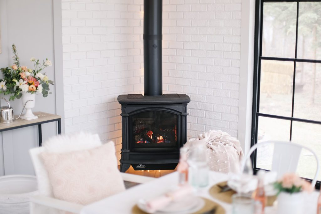 A cozy stove lit beside Mother's Day tablescape in white brick and black window sun room