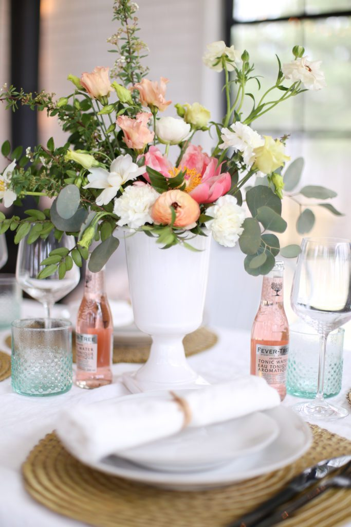 Natural, loosely arranged floral arrangement in a white pedestal vase sitting on a table with pink water bottles and a white table cloth.