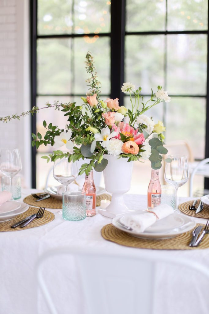 Table setting with pink bottles, white dishes, seagrass place mats and fresh flower arrangement